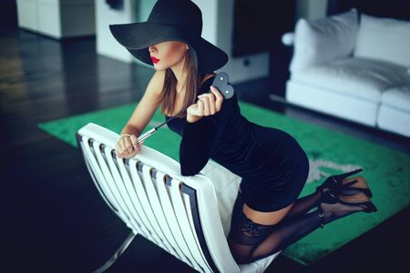 Sexy young dominant femme fatale with whip kneeling on sofa Stock fotó