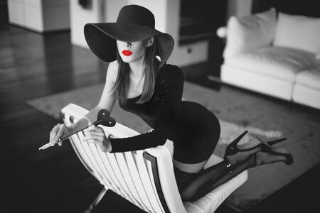 Sexy dominant femme fatale in hat holding whip with red lips on sofa, kneeling, black and white selective coloring Stock fotó