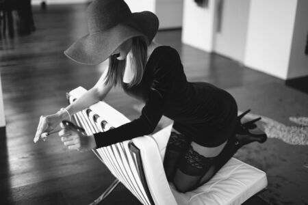 Sexy dominant femme fatale in hat holding whip on sofa, kneeling and looking down, black and white