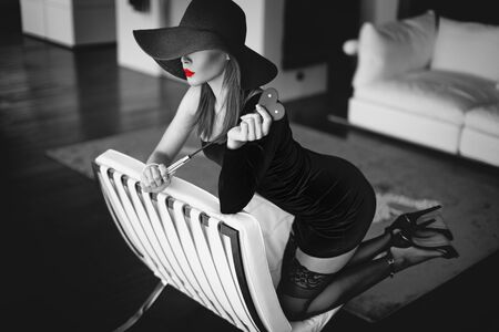 Sexy young dominant femme fatale with whip kneeling on sofa black and white, selective coloring