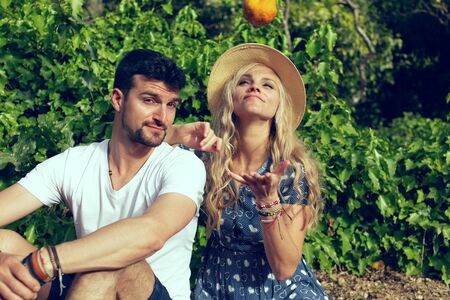 Young woman in hat toss up an orange with boyfriend in nature