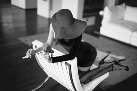 Sexy dominant femme fatale in hat holding whip on sofa, covering face and kneeling, black and white Stock fotó