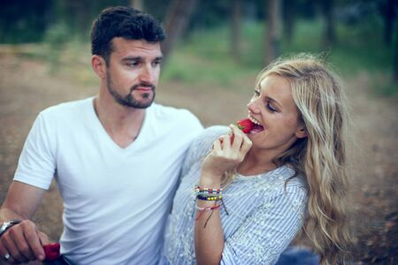 Young seductive woman eating strawberry and flirting with man on picnic