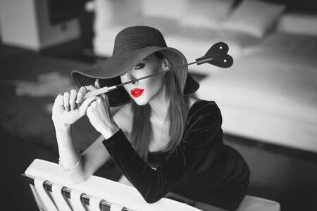 Passionate dominant femme fatale in hat holding whip in front of face, kneeling on white leather chair in luxury flat, black and white with red lips, selective coloring 免版税图像