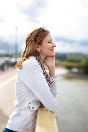 Young carefree woman thinking about love on bridge, outdoors