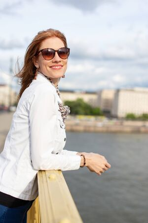 Young fashionable redhead woman in sunglasses smiling on bridge, Budapest, Hungary Stock fotó