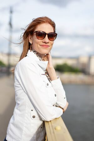 Young fashionable woman in sunglasses smiling on bridge, portrait at autumn, Budapest, Hungary Stock fotó
