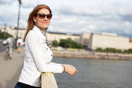 Young fashionable woman in sunglasses smiling on bridge, Budapest, Hungary