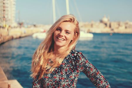 Happy young positive blonde woman smiling at Mediterranean sea portrait
