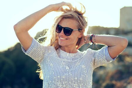 Happy young caucasian blonde woman playing with hair in sunset Stock fotó