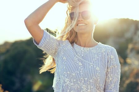 Young caucasian blonde woman playing with hair in sunset