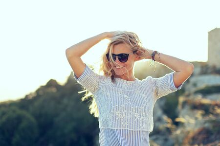 Happy young natural caucasian blonde woman in sunglasses playing with hair in sunset