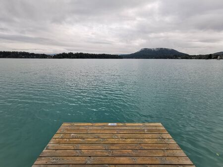 Tranquil green lake with pier, Faaker See, Austria, Europe