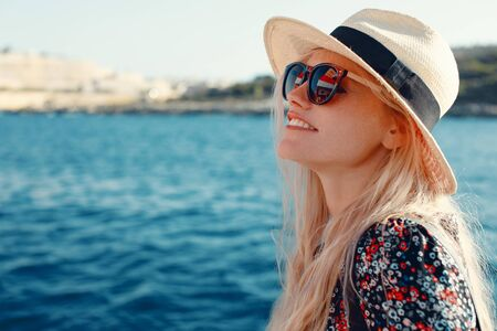 Happy blonde Mediterranean woman in hat amazed by panorama on cruise ship Stock fotó