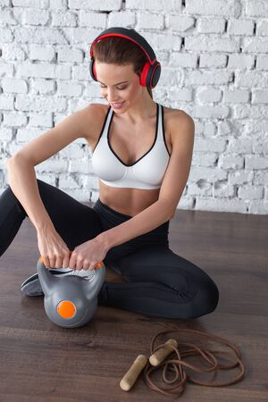 Woman listening music by headphones during workout, sitting on floor, looking down