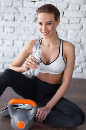 Happy sporty woman holding bottle water after workout, hydration