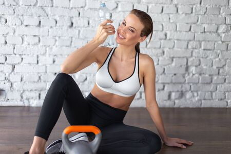 Fit woman holding bottle of water, hydration, sitting on floor