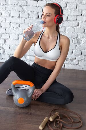 Woman hydrating after workout on floor, drinking water Stock fotó