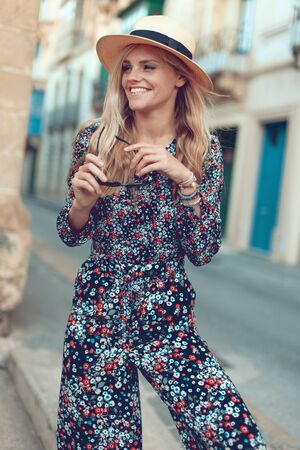 Happy young fashionable blonde woman posing at Mediterranean street, looking away
