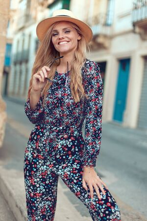 Happy young fashionable blonde woman posing at Mediterranean street, in hat, toothy smile