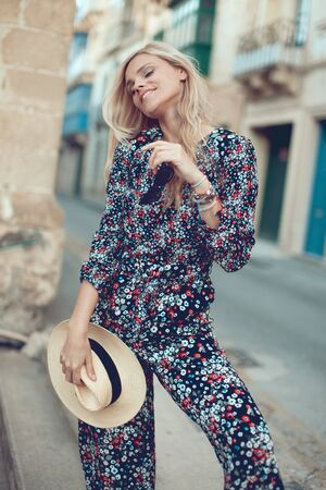 Happy young fashionable blonde woman posing at Mediterranean street, eyes closed Stock fotó