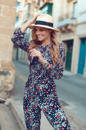 Happy young fashionable blonde woman posing at Mediterranean street, holding hat, looking away