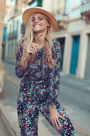 Happy young fashionable blonde woman posing at Mediterranean street, laughing