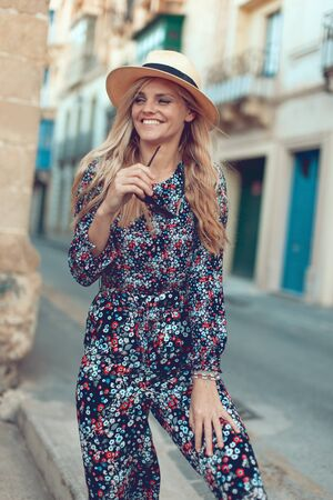 Happy young fashionable blonde woman posing at Mediterranean street, positive Stock fotó