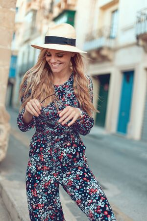 Happy young fashionable blonde woman posing at Mediterranean street, femininity