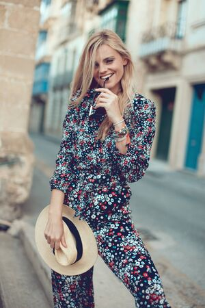 Happy young fashionable blonde woman posing at Mediterranean street, biting sunglasses