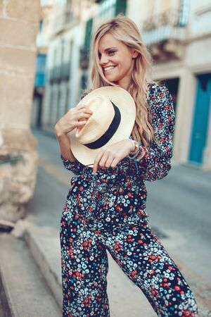 Happy young fashionable blonde woman posing at Mediterranean street, cheerful