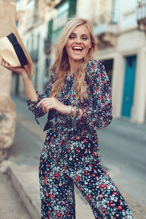 Happy young fashionable blonde woman posing at Mediterranean street, say hi, laughing