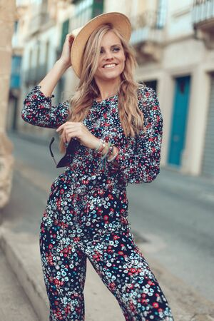 Happy young fashionable blonde woman posing at Mediterranean street, holding hat Stock fotó