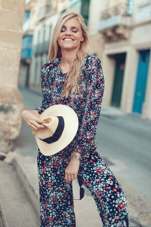 Happy young fashionable blonde woman posing at Mediterranean street, daydreaming Stock fotó
