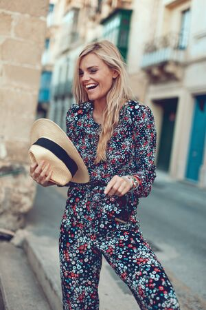 Happy young fashionable blonde woman posing at Mediterranean street, laughing and looking away Stock fotó
