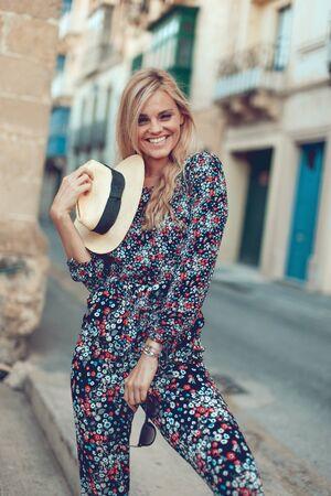 Happy young fashionable blonde woman posing at Mediterranean street posing Stock fotó