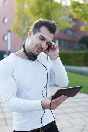 Young handsome guy listening music by headphones in park, enjoying rythm