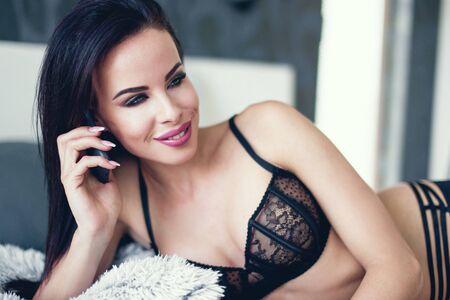 Sexy brunette woman in underwear calling by phone in bed Stock fotó
