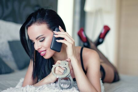 Sensual dominant erotic woman calling by phone in bed, holding handcuffs, BDSM Stock fotó