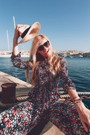 Happy young blonde Mediterranean woman enjoying sightseeing at sea, holding hat