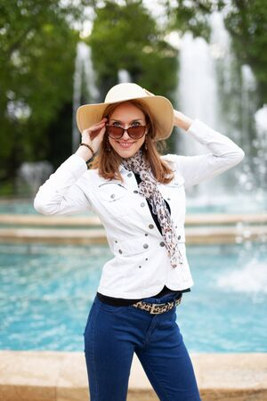 Happy young natural woman at park with fountain holding sunglasses and hat, Budapest, Margaret Island, Hungary 版權商用圖片