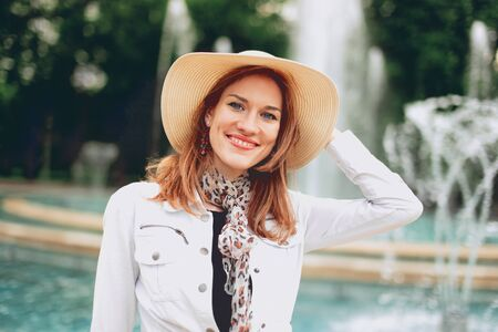 Happy young woman in hat at park with fountain portrait, Budapest, Margaret Island, Hungary