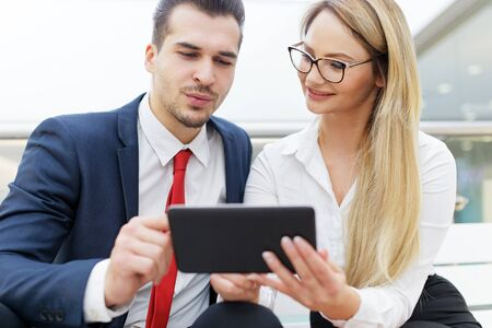 Successful young businesspeople analyzing financial situation on digital tablet indoors