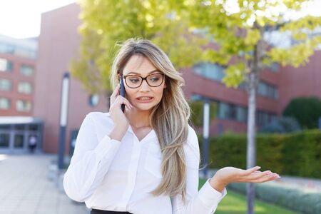 Blonde businesswoman apologizing while calling outdoors Imagens