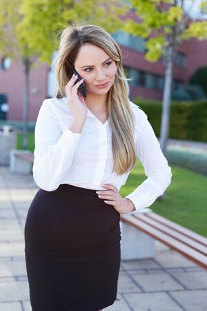 Young blonde businesswoman calling in park by phone, looking away Stockfoto
