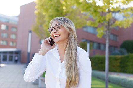Happy young caucasian blonde businesswoman calling in park