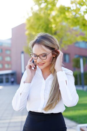 Happy young blonde businesswoman in eyeglasses calling in park, looking down