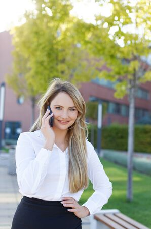 Young blonde businesswoman calling and smiling in park, looking at camera Stockfoto