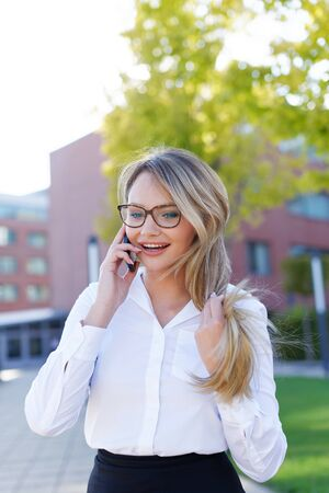 Happy young blonde businesswoman in eyeglasses calling in park Stockfoto