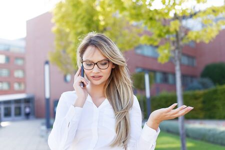 Clever blonde businesswoman explain while calling outdoors